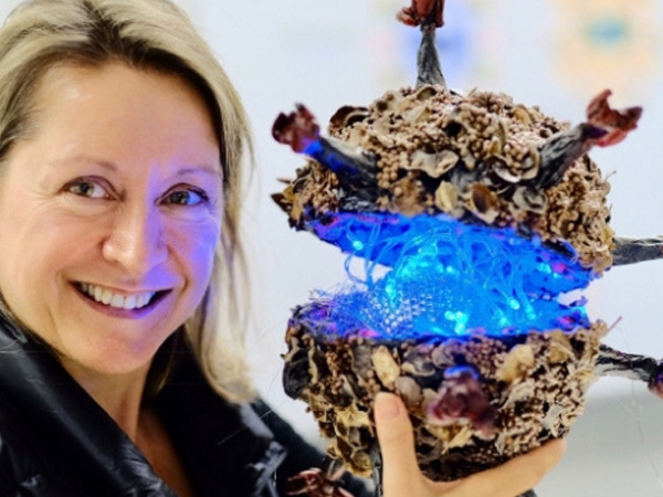 Dr Erica Tandori, legally blind artist with her model of HIV.